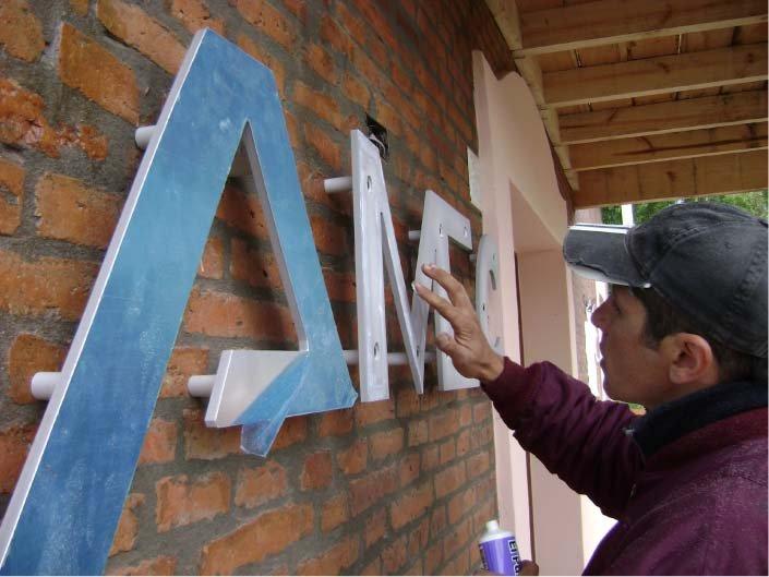 RA Trabajando - Pegando componente de aluminio - Cartel corpóreo - AMEC - OSECAC - El Bolsón - Provincia de Río Negro - RA Carteles